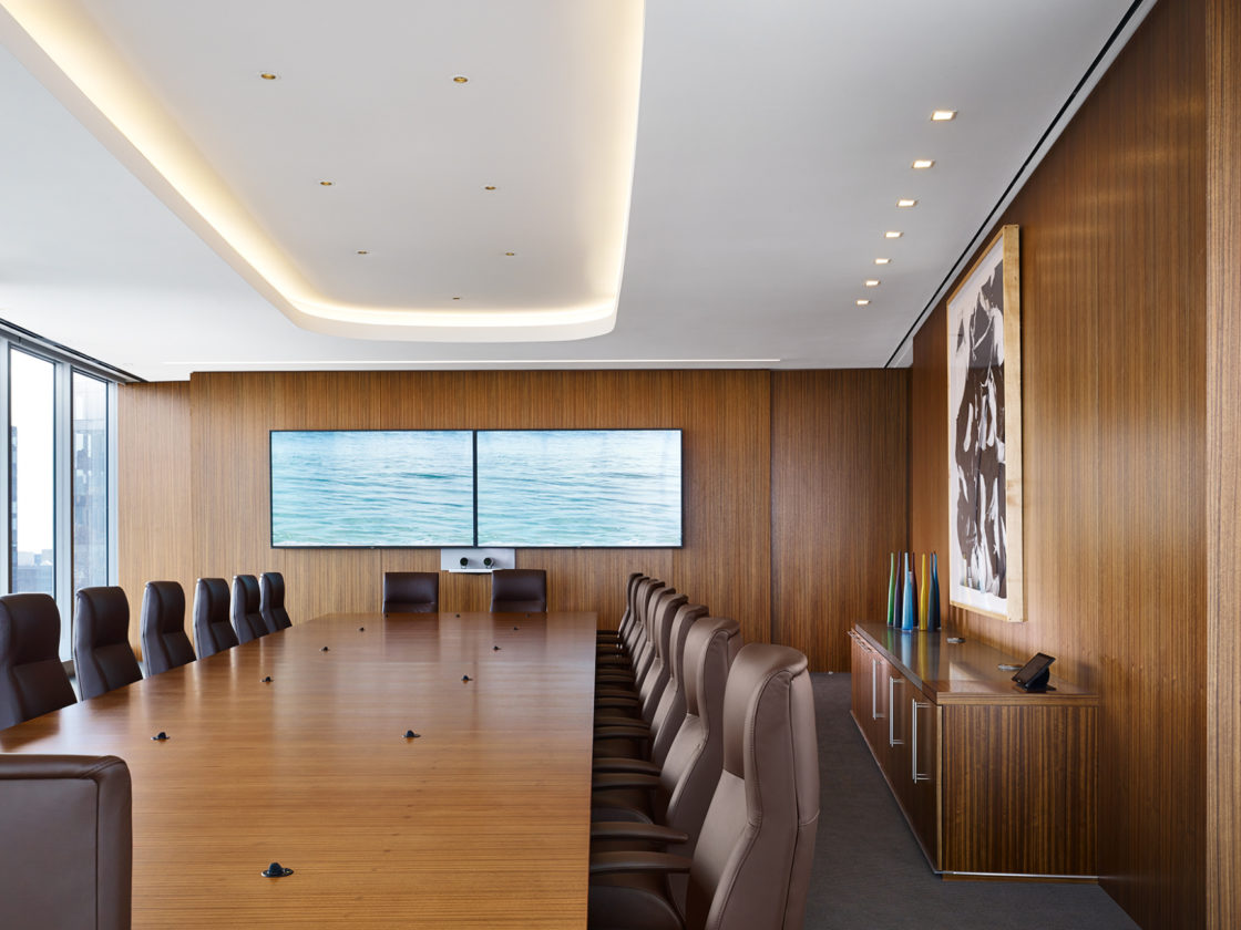 McDermott boardroom with seating around a conference table facing a monitor.