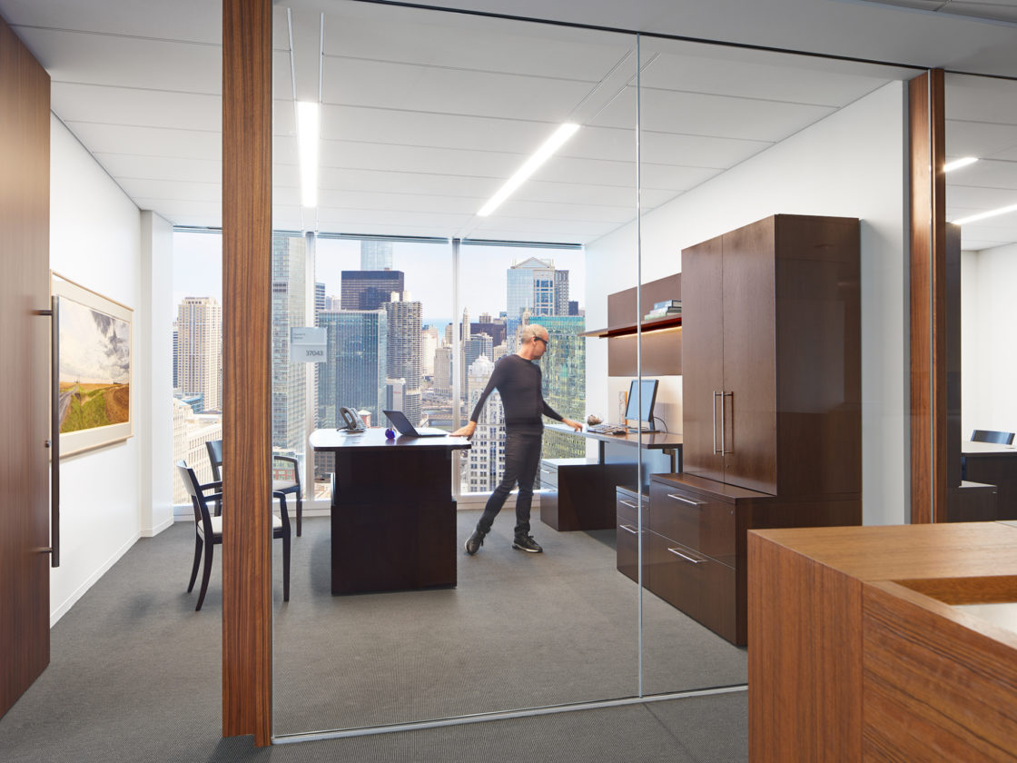 McDermott private office with wood case goods and height adjustable desks.